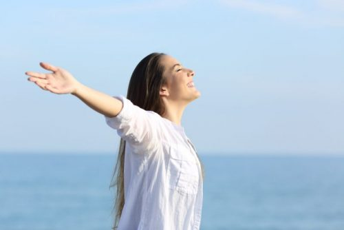 Positive woman raising her arms in happiness