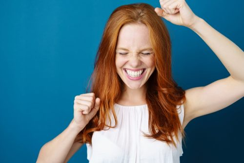 red head woman cheering and excited against blue background